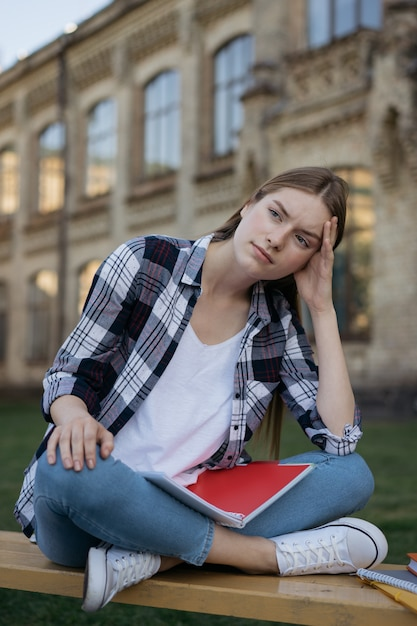 Student disappointed by exam results. unhappy woman with tired face sitting on bench, exams failure Premium Photo