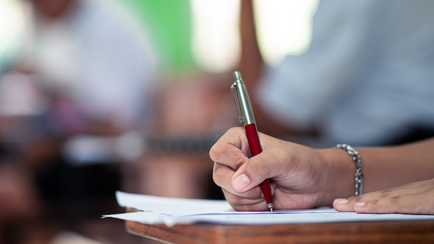 Student doing an exam with stress in school classroom Premium Photo
