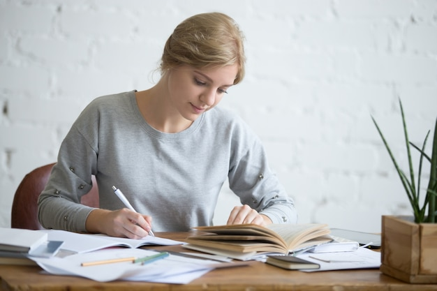 Student female performing a written task in a copybook Free Photo