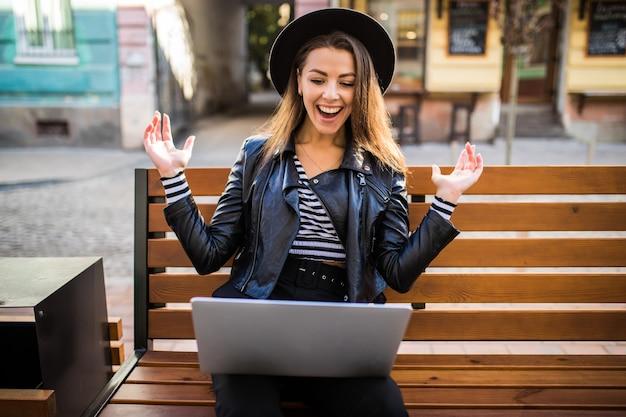 学生の女の子のビジネス女性は秋の公園の街の木製のベンチに座っています 無料写真