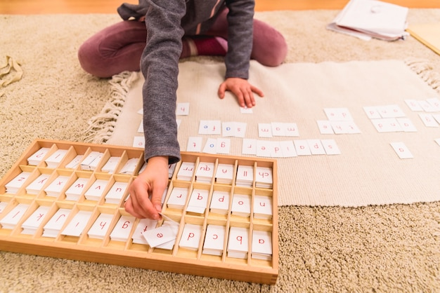 Student girl hand using cards with letters to compose words, sitting on the classroom floor of her montessori school. Premium Photo