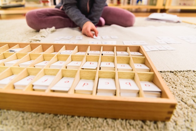 Student girl hand using cards with letters to compose words Premium Photo