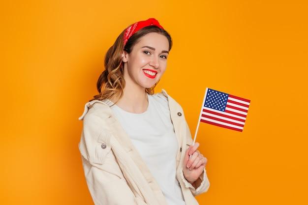 学生の女の子は小さなアメリカの国旗とオレンジ色の背景に分離された笑顔を保持しています。 Premium写真