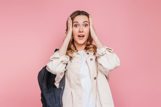 Студентка в белой куртке с вьющимися волосами и рюкзаком удивила потрясенное лицо молодой женщины, держащей руки на лице, изолированной на розовой стене Premium Фотографии