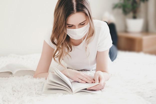 自宅で医療マスクのベッドで横になっていると、本、検疫、コロノウイルス、分離を読んでいる学生の女の子 Premium写真