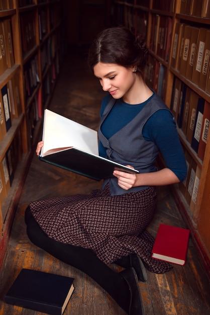 大学図書館で開いた本を持つ学生少女。 Premium写真