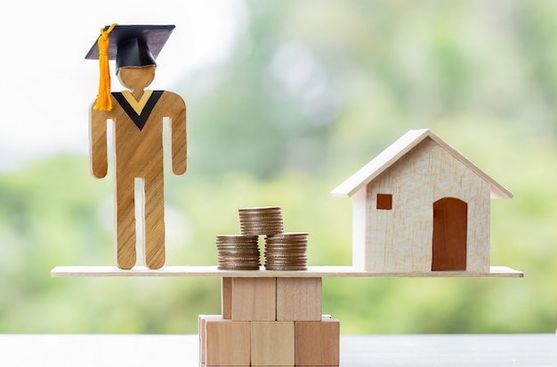 Student graduation, coins and house on wood balance. concept of study requires money cost saving Premium Photo