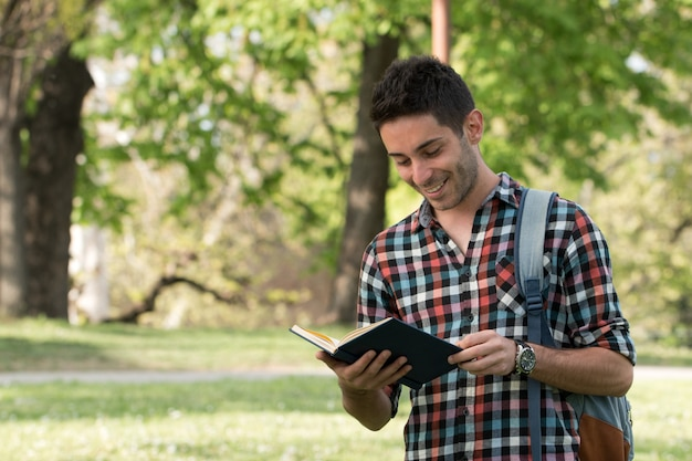 Student guy doing homework in the park. Premium Photo
