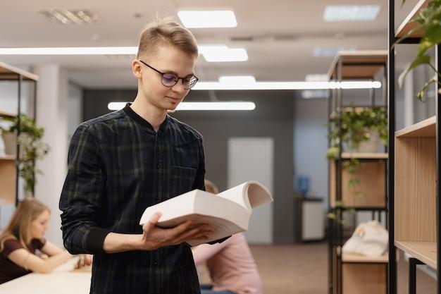 Un uomo studente raccogliendo libri dallo scaffale Foto Gratuite