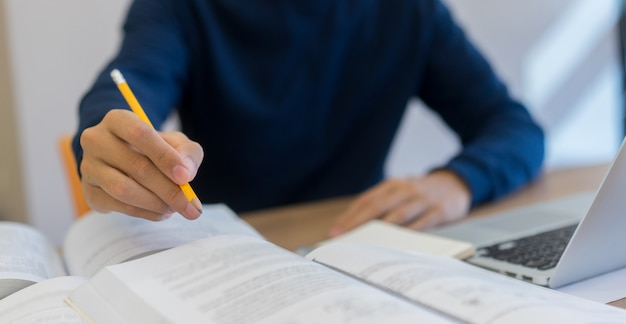 Student man using pencil for lecture on text book in library Premium Photo
