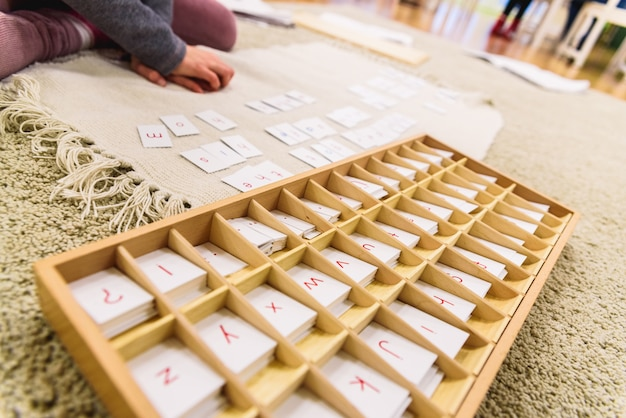 A student of a montessori school using cards with letters Premium Photo