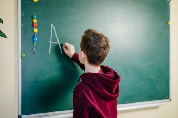 高校の生徒が教室の緑の黒板の近くの暗いパーカーに立っています。 10代の少年は、ボードにアルファベットを書いています。学校教育のコンセプトです。 Premium写真