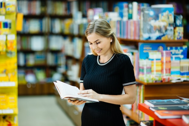 Student reading a book in the library Premium Photo