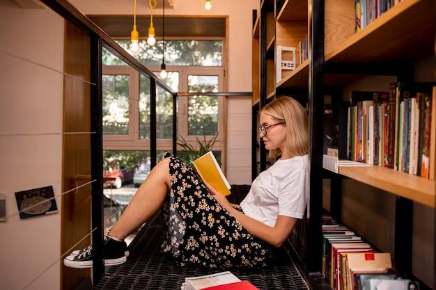 Studente che legge un libro in biblioteca Foto Gratuite