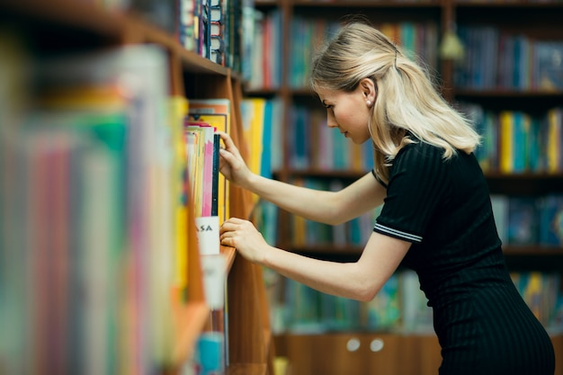 Student searching for books in a library Premium Photo