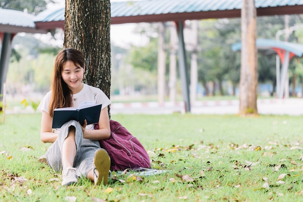 Student Sitting Under A Tree In School And Reading A Book