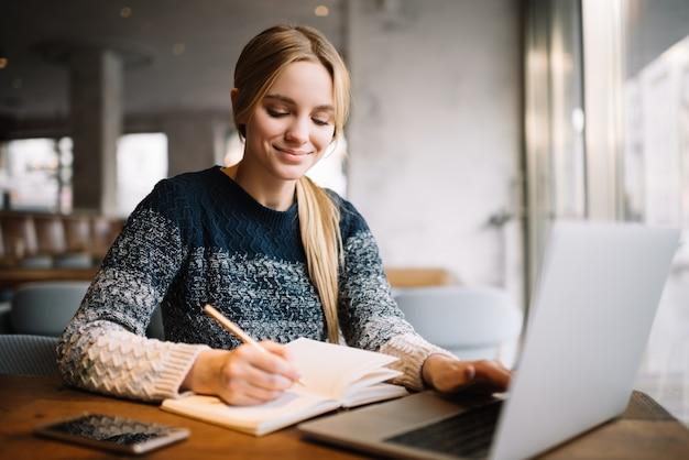 Студент учится, используя портативный компьютер, онлайн-обучение. красивая женщина-фрилансер пишет заметки, планируя рабочий проект, работая дома Premium Фотографии