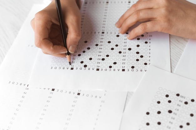 Student uses a pencil for an exam test Premium Photo