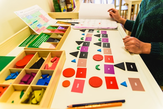 Student using material to learn geometric shapes in a montessori school. Premium Photo