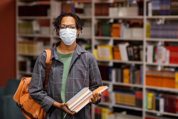 Studente che indossa una maschera medica in biblioteca Foto Gratuite
