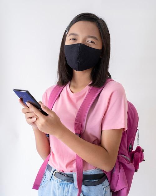 Студент с маской для лица со смартфоном в розовой рубашке Premium Фотографии