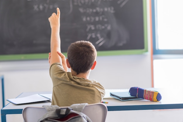 Student with hands up in classroom during a lesson Premium Photo