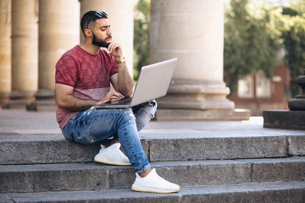 Student with laptop by the university Free Photo