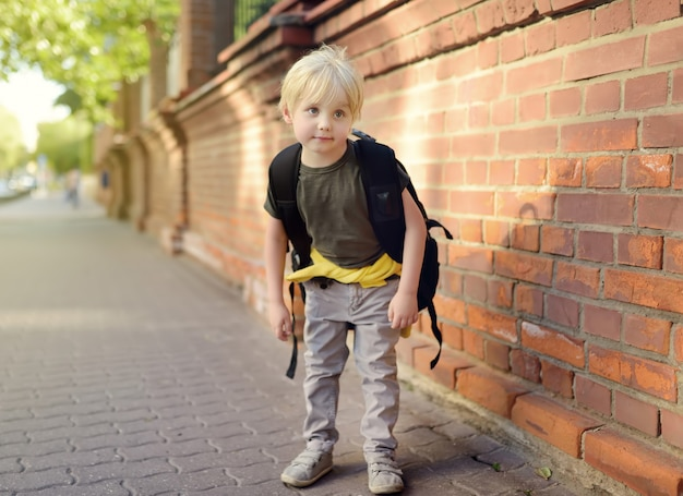 Student with large backpack near the school building. Premium Photo