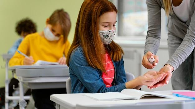 Студент с медицинской маской получает дезинфицирующее средство для рук от учителя Бесплатные Фотографии