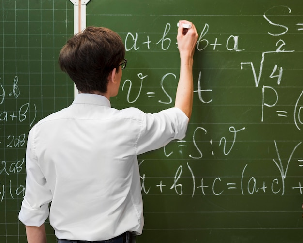 Student writing on chalkboard Free Photo