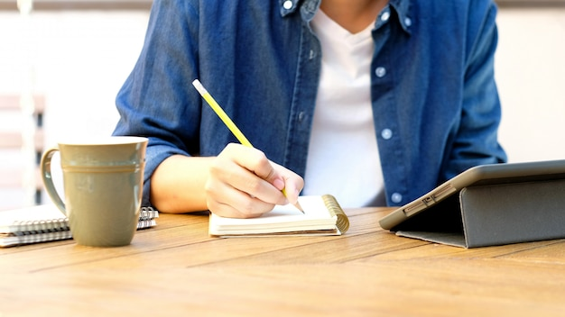 Student writing on notebook while using digital tablet Premium Photo