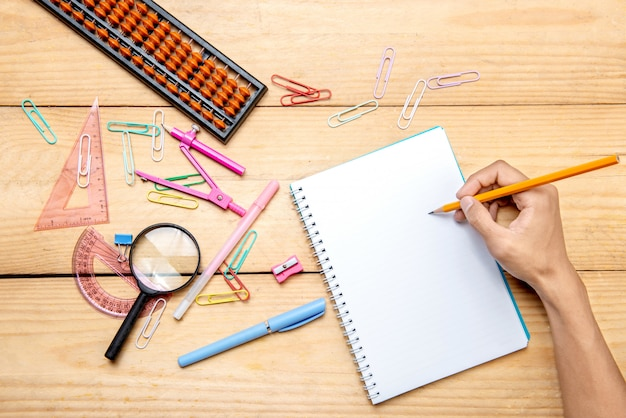 Student writing in notebook with school supplies and stationery on the wooden table Premium Photo