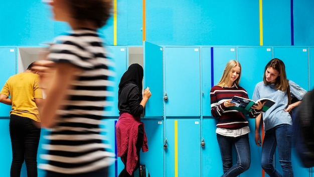 Students chilling and walking by the lockers Premium Photo