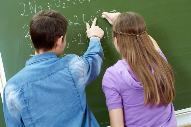 Students doing maths problems on blackboard Free Photo