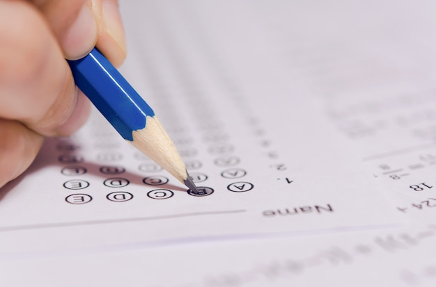 Students hand holding pencil writing selected choice on answer sheets Premium Photo