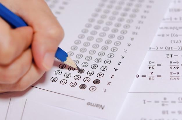 解答用紙と数学の質問用紙で選択した選択肢を鉛筆で書く学生の手。 Premium写真