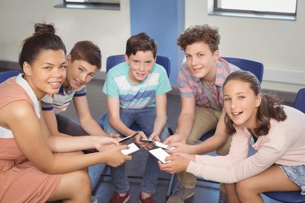教室で携帯電話を持つ学生 Premium写真
