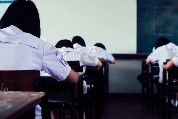 Students reading and writing answer doing exam in classroom. Premium Photo