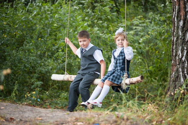 Students ride on the swing after school in school uniform. Premium Photo