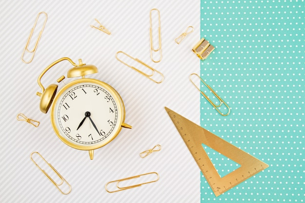 Students and school golden supplies with alarm clock. back to school and office stationery idea Premium Photo