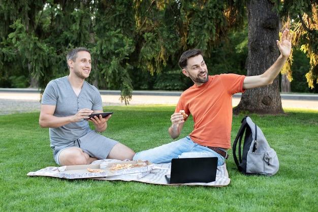 Студенты, сидящие в городском парке, используя ноутбук, работая на открытом воздухе, показывая приветственный жест. счастливый молодой человек улыбается и машет друзьям. студенты учатся в парке и улыбаются. дружба, учеба, Premium Фотографии