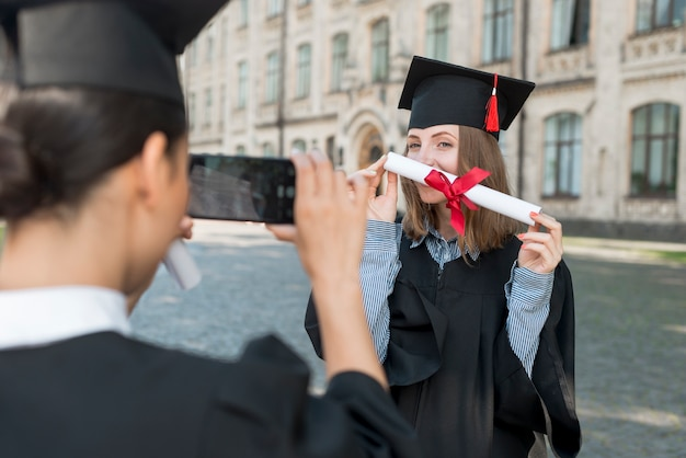 Students taking photo of each other at graduation Free Photo