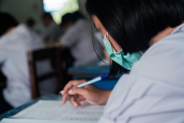 コロナウイルスまたはcovid-19を保護するためにマスクを着用し、ストレスのある学校の教室で試験解答用紙の演習を行う生徒。 Premium写真
