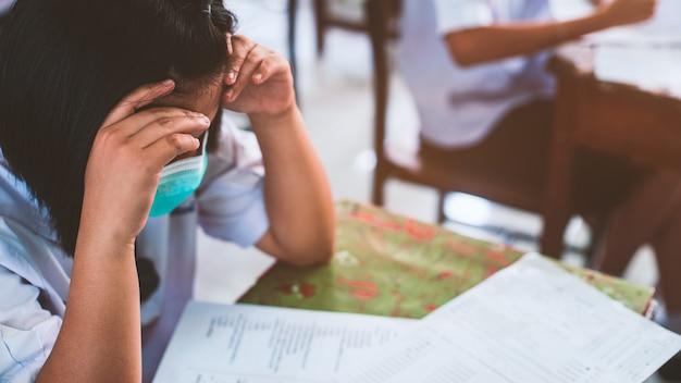 コロナウイルスやcovid-19を保護するためのマスクを着用し、ストレスのある学校の教室で試験解答用紙の演習を行う生徒。 Premium写真