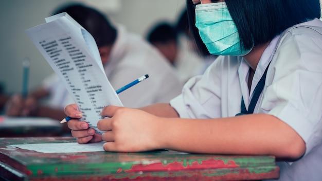 コロナウイルスまたはcovid-19を保護するためにマスクを着用し、試験解答用紙の演習を行う学生 Premium写真