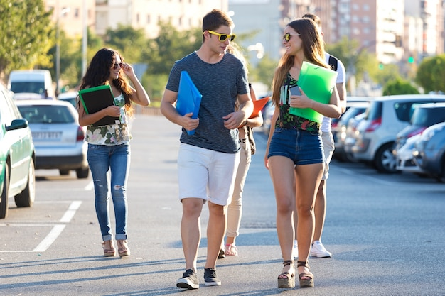 Students with folders walking through street Free Photo