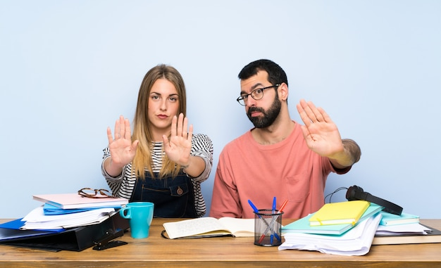 Students with many books making stop gesture and disappointed Premium Photo
