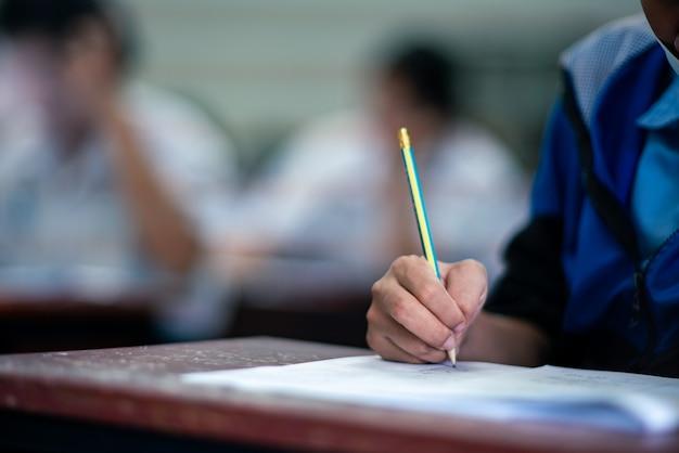 스트레스를받는 학교 교실에서 시험 답안지를 쓰고 읽는 학생들 프리미엄 사진