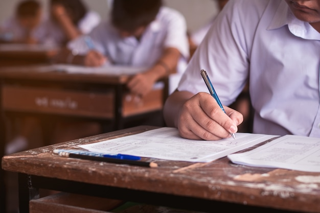 Students writing answer doing exam in classroom . Premium Photo