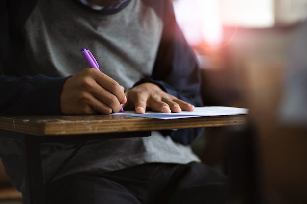 Students writing pen in hand doing exams answer sheets exercises in classroom with stress. Premium Photo